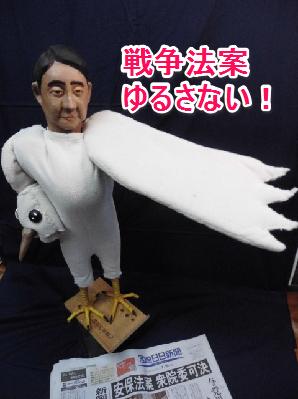 鳩の着ぐるみを着て、憲法を踏みつける鷹の像